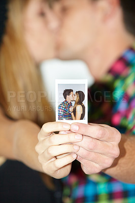 Buy stock photo A young kissing couple holding up a photo booth photograph of them kissing