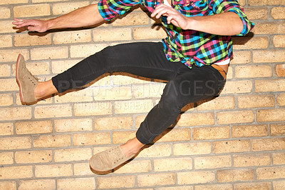 Buy stock photo A cropped shot of a young man jumping with two feet through the frame in front of a brick wall