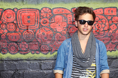 Buy stock photo Portrait of a stylish young man standing in front of a graffiti filled wall