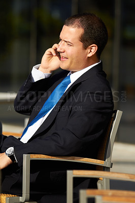 Buy stock photo A businessman sitting on a chair and talking on his cellphone