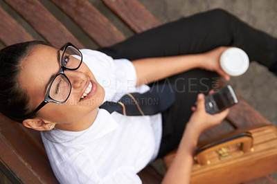 Buy stock photo A beautiful young woman winking at the camera while sitting on a bench with her cellphone, coffee and satchel