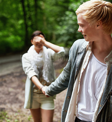 Buy stock photo A girl covering her eyes with her hand is led through the forest by her boyfriend