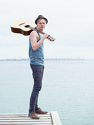 Buy stock photo A full length shot of a stylish young man carrying a guitar and standing on a dock near water