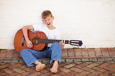 Buy stock photo Musical young boy strumming his guitar while sitting against a wall and singing along