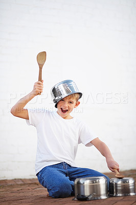 Buy stock photo Noisy young boy playing drums on a set of pots using wooden spoons