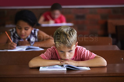 Buy stock photo A young boy resting his head on his arms as he sits in a classroom looking bored
