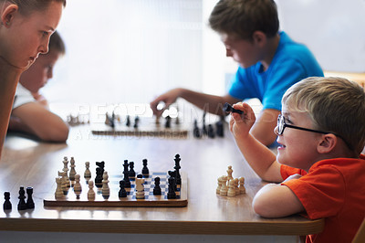 Buy stock photo Young boy wearing spectacles and playing chess with an older child