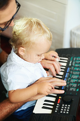 Buy stock photo Cute little boy being taught how to play the piano