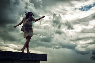 Buy stock photo Young woman walking on a rooftop with her arms outstretched