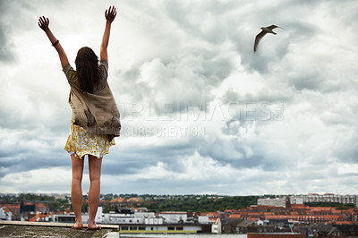 Buy stock photo Rear view of a young woman with her arms raised standing on a rooftop