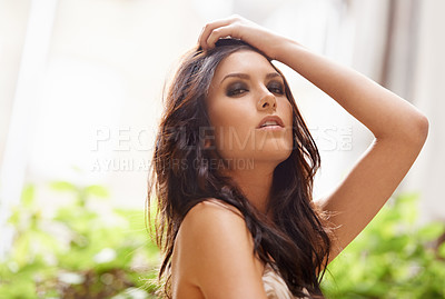 Buy stock photo A gorgeous young woman standing with her hand in her hair outside