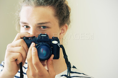 Buy stock photo Young man with his hair in a bun looking at you and holding up his camera