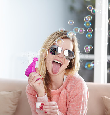 Buy stock photo Quirky young woman playing with a bubble gun and sticking out her tongue