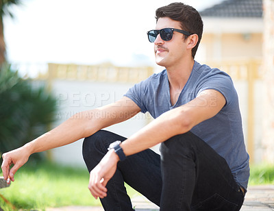 Buy stock photo Trendy young hipster having a cigarette while sitting outdoors