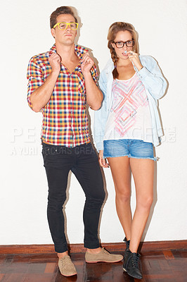 Buy stock photo Stylish young hipster couple standing against a white wall while wearing glasses