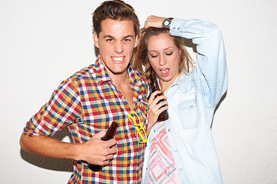 Buy stock photo Young hipster couple drinking and partying against a white wall