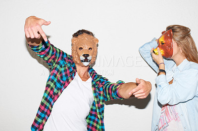 Buy stock photo Young hipster guy wearing a lion mask and gesturing alongside a young woman wearing a bear mask