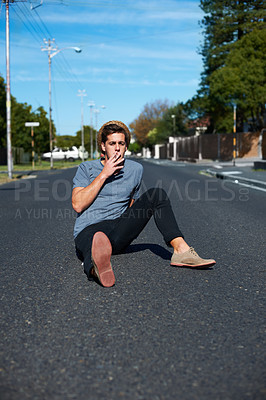 Buy stock photo Young hipster guy sitting in the middle of the road and smoking