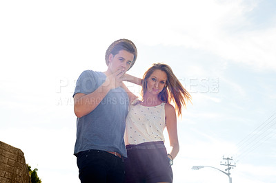 Buy stock photo Young hipster couple standing outdoors against a bright sky