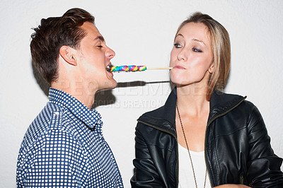Buy stock photo Young hipster woman feeding her boyfriend a striped lollipop