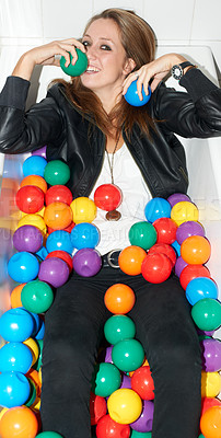 Buy stock photo Attractive young hipster girl lying in a bath tub of colorful plastic balls