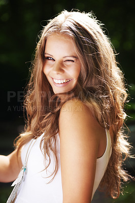 Buy stock photo Portrait of a beautiful young woman winking at you in a green forest