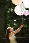 A pretty young woman holding a bunch of balloons in the forest