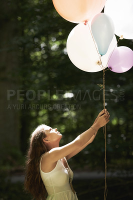 Buy stock photo A pretty young woman holding a bunch of balloons in the forest