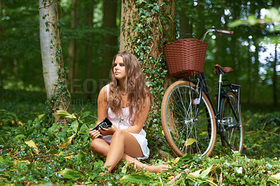 Buy stock photo A young girl sitting at the foot of a tree with her bike and camera
