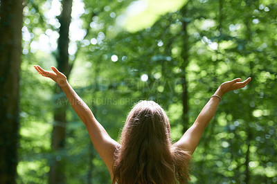 Buy stock photo Rearview of a beautiful young woman with her arms raised while standing in a forest