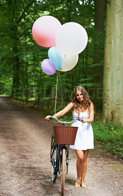 Buy stock photo A pretty young woman with a bunch of balloons and a bicycle walking in the forest
