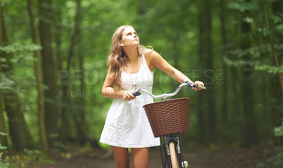 Buy stock photo A pretty young woman walking in the forest with her bicycle