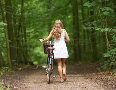 Buy stock photo Rear view of a young woman walking in the forest with her bicycle