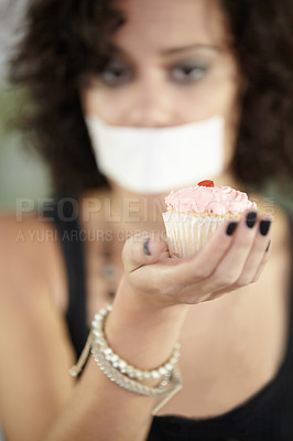 Buy stock photo A young woman holding baked goods with her mouth covered