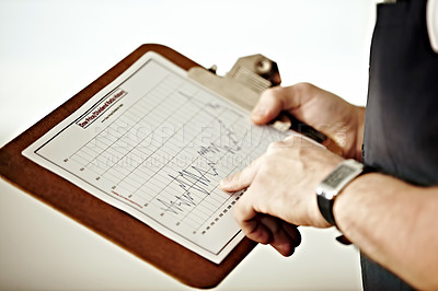 Buy stock photo A person pointing at a graph on a clipboard