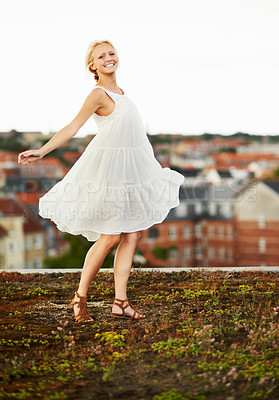 Buy stock photo A beautiful young woman twirling outside with a city in the background
