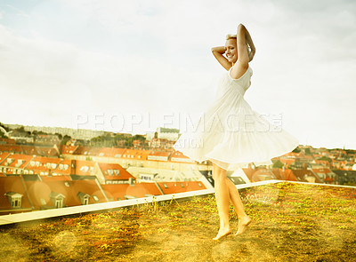 Buy stock photo Gorgeous young woman dancing on a rooftop surrounded by bokeh