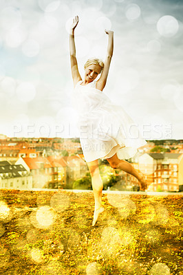 Buy stock photo Beautiful young woman jumping on a rooftop with a city in the background surrounded by bokeh