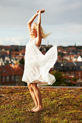 Buy stock photo A gorgeous young woman dancing with the city in the background
