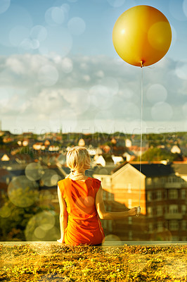 Buy stock photo Rear view of a young woman sitting with a balloon and a city in the background