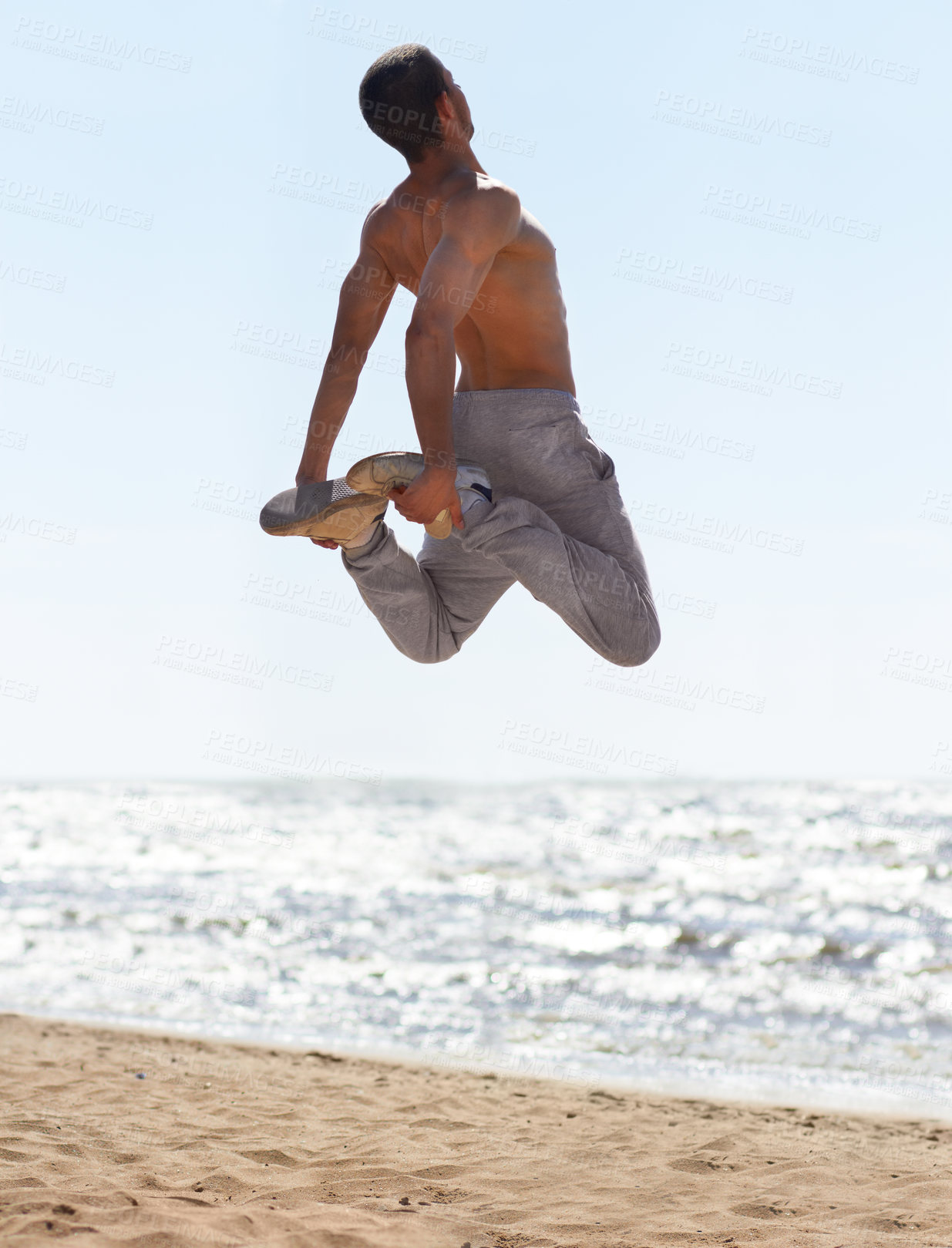 Buy stock photo An athletic young man practicing parkour on the beach