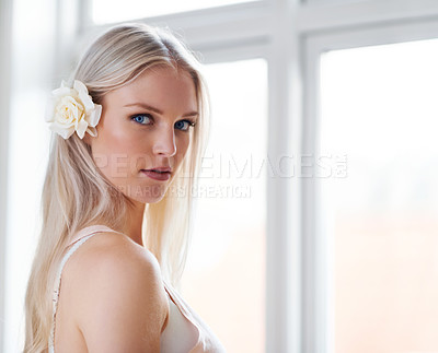 Buy stock photo Portrait of an attractive woman with a white rose in her hair while standing in her bedroom