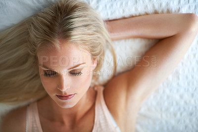Buy stock photo An attractive young woman lying with her eyes closed on her bed