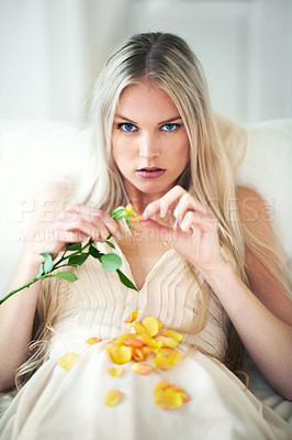 Buy stock photo Portrait of an attractive woman pulling petals from a rose on her bed