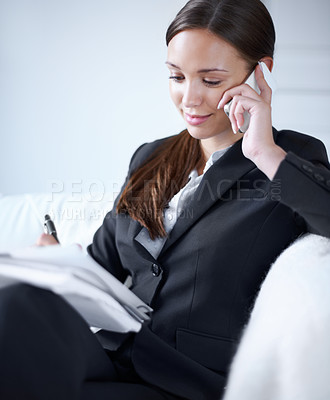 Buy stock photo Attractive young businesswoman working at home while using her cellphone