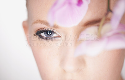 Buy stock photo A beautiful young woman looking out from behind an orchid