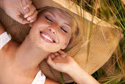 Buy stock photo Beautiful young woman wearing a straw hat and lying in a field