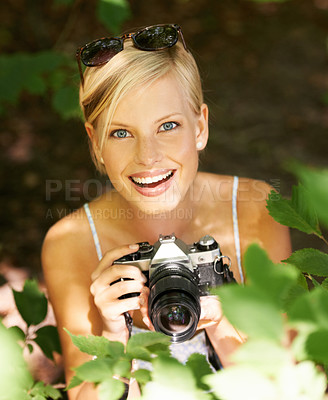 Buy stock photo Pretty young photographer in the woods getting ready to take a shot