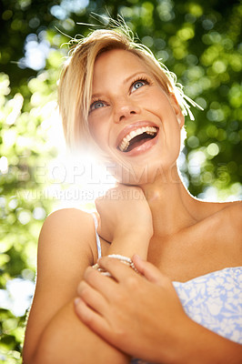 Buy stock photo Pretty young blonde woman laughing while standing in a forest