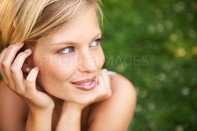 Buy stock photo Attractive young blonde woman sitting and smiling on the grass outside